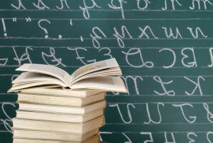 Books and blackboard with cursive letters stock photo